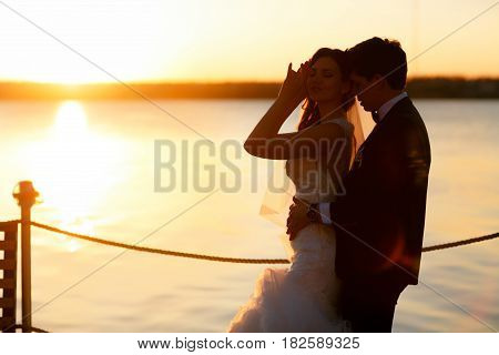 Groom Leans To A Bride From Behind Standing In The Front Of A Sunset