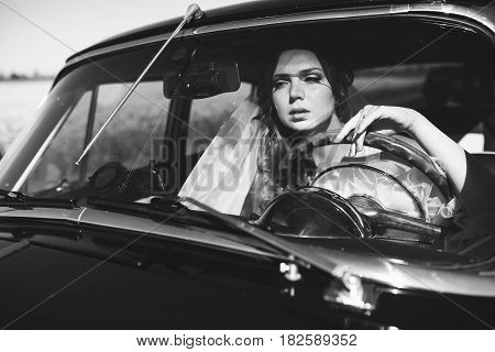 A black and white picture of a bride sitting at the front seat in a car