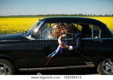 Groom Kisses A Bride Reaching To Her From The Back Seat Of A Car