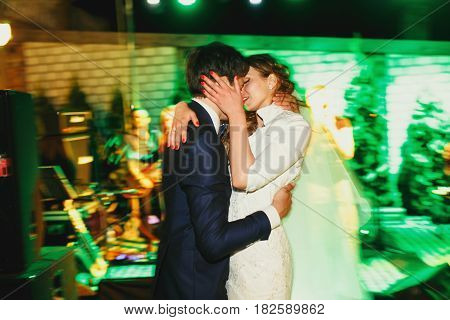 A Blurred Picture Of Newlyweds Kissing On The Dancefloor