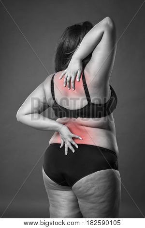 Back and neck pain fat woman with backache overweight female body on gray background black and white photo with red spots