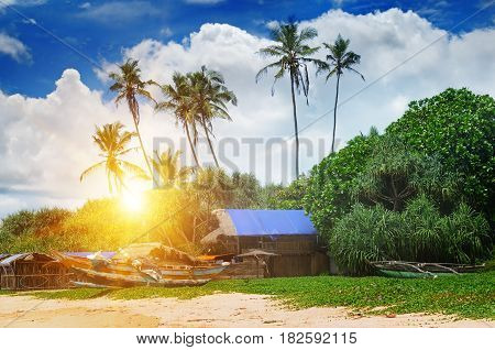 old fishing boats and huts on sandy beach and sunset