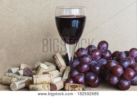 glass of red wine, corks and grapes