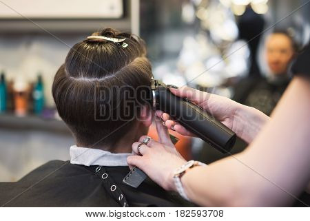 Stylish fashionable young girl in a hairdresser.In the hairdresser's girl make a hairstyle with a machine shaving whiskey. In the hands of a master hair clipper.