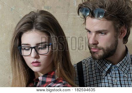Young nerd couple of students in geek glasses. Pretty girl or beautiful woman with long hair and handsome man with beard in checkered shirts on beige background. Education and knowledge
