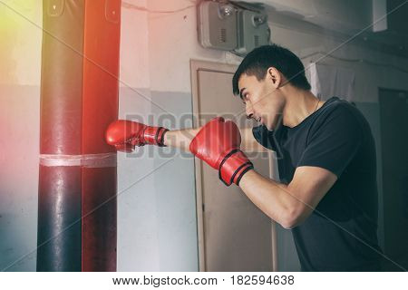 A young man is boxing a bag. Hits. Beautiful, toned