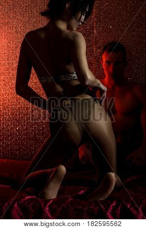 young couple of handsome macho man with muscular body and pretty woman or sexy girl in stockings or tights and bra on red blanket on abstract wall background