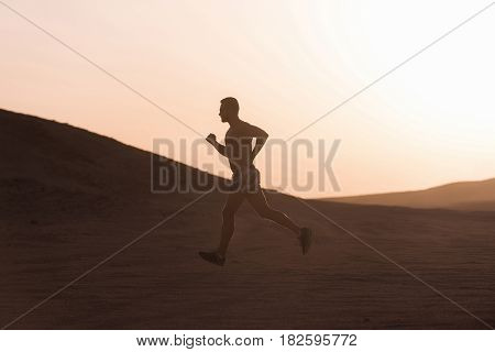 man runner or fit male athlete running in desert sand dune at mountain in sun ray at sunset sunrise outdoor on white sky background. sprinting healthy lifestyle success sport and marathon workout