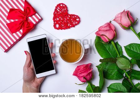 Festive Table: Roses, A Smartphone And A Cup Of Hot Tea.