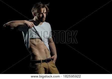 Handsome man or unshaven macho bodybuilder with stylish blond hair haircut in white tshirt showing sexy muscular torso with six packs and abs biceps triceps striptease on black background