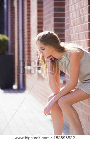 Waiting and loneliness. Pretty girl or young woman teenager with adorable pensive face and stylish blond long hair in fashion dress sitting on window sill of brick building on sunny summer day