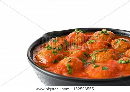Meatballs with tomato sauce in iron frying pan isolated on white background