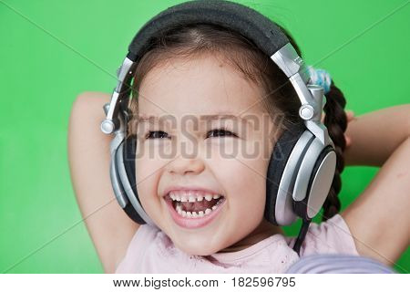 Portrait of asian girl with headphones, green background