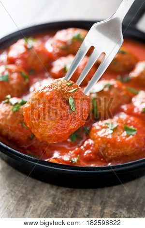 Meatballs with tomato sauce in iron frying pan on wooden table