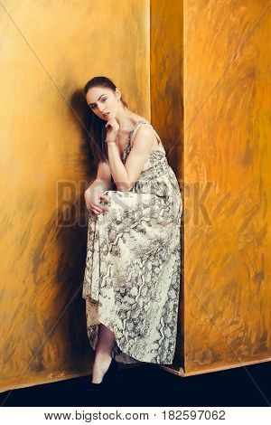 Pretty Girl With Raised Leg Leaning On Wall