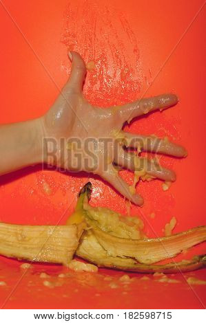 hand of girl squeezing juice or squash from banana ripe mellow fruit with peeled yellow skin and drops splashes on bright orange background. Vitamin and healthy eating