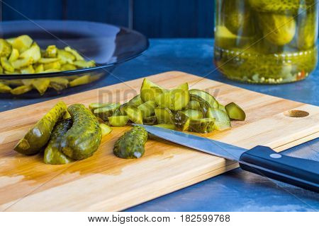 Cucumbers Or Pickled Gherkins With A Knife On A Wooden Cutting Board. Blue Gray Background. Bank Wit