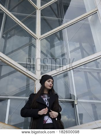 Young beautiful girl with long hair wearing a hat and a blue coat against the background of a glass building