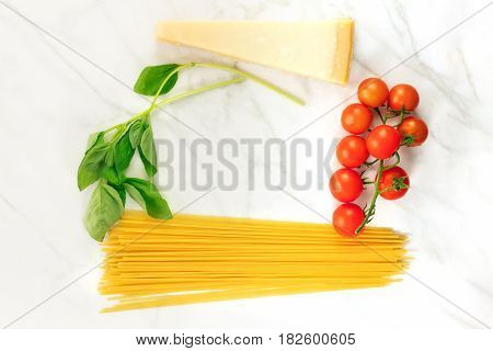 An overhead photo of basic pasta ingredients on a white marble table. Fresh cherry tomatoes, a slice of cheese, spaghetti, and basil leaves, forming a frame for text