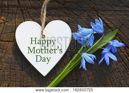 Happy Mother's Day.First spring flowers and decorative wooden heart on old wooden background.Mother's Day greeting card.Selective focus.