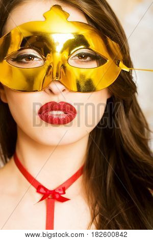 luxury and success pretty woman or cute sexy girl in golden carnival mask has brunette hair and red lips makeup on adorable face with ribbon on neck. fashion party and holiday celebration