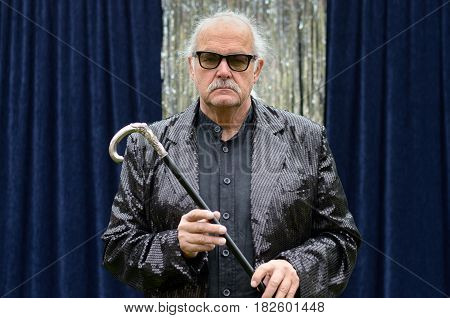 Deadpan Stage Performer Holding A Cane