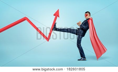 A businessman in a red superhero cape beating a red statistic arrow with his foot. Business and profit. Credit and loss. Financial improvement.
