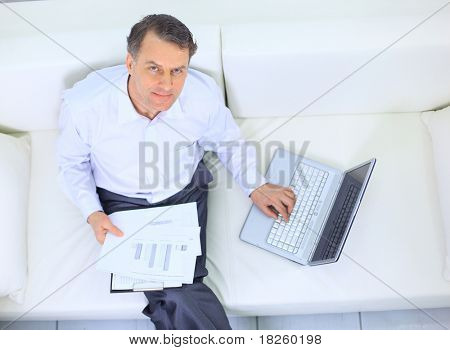 Senior businessman sitting on sofa and using laptop
