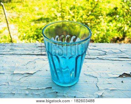 Blue vintage wine glass on the window.