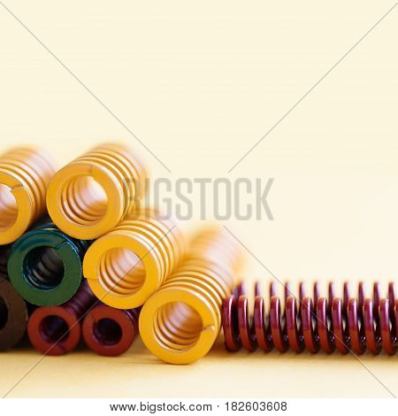 Metal springs colorful steel spirals coil with different hardness flexibility sizes. yellow background, soft focus shallow depth of field.