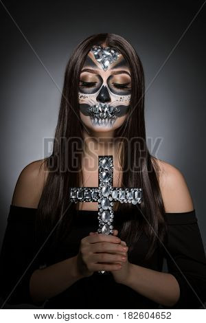 Woman with smart artistic makeup in horror style posing in studio carrying rhynestone cross in her hands