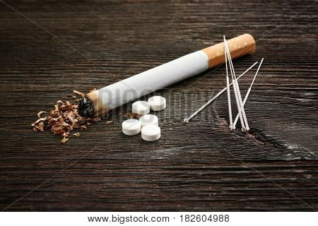 Cigarette with needles and pills on table