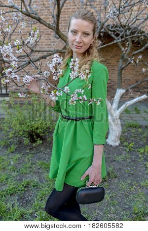 Young blonde girl on the background of a spring blooming garden