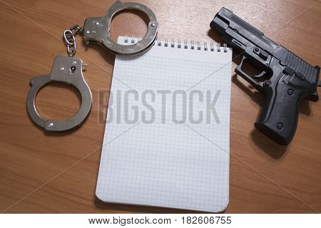 Handgun Handcuffs And Notepad On The Table With Copy Space