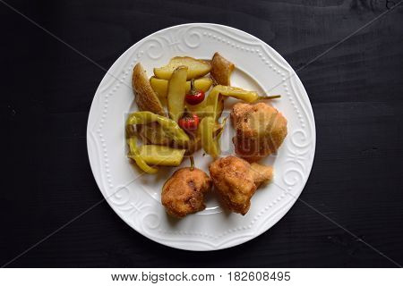 cauliflower fried in batter  on wooden black  background and potatoes.Healthy food