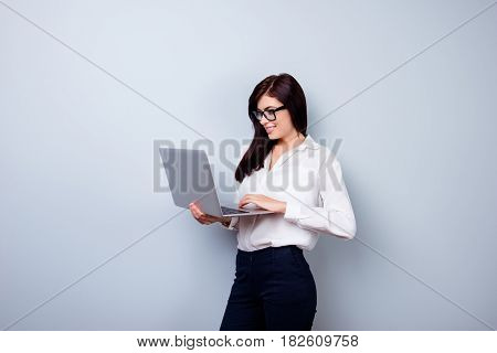 Photo Of Charming Businesslady Holding Laptop And Typing Sms To Her Business Colleagues