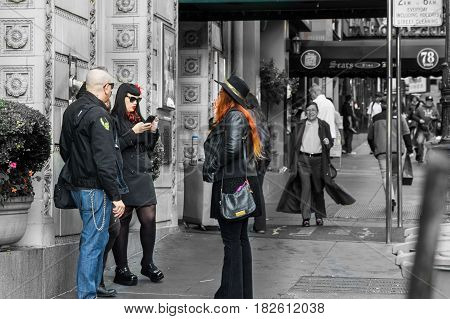 San Francisco, USA -October 29, 2016; Group three interesting   and different people standing waiting outside building in Powell Street,