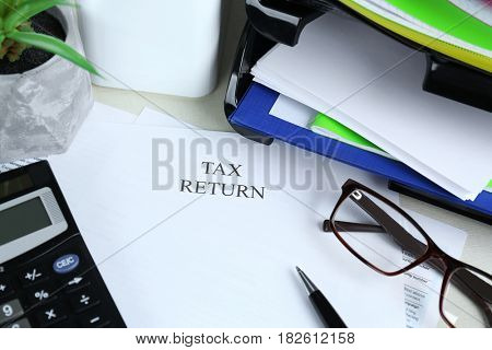Paper with printed TAX RETURN text and stationery on table