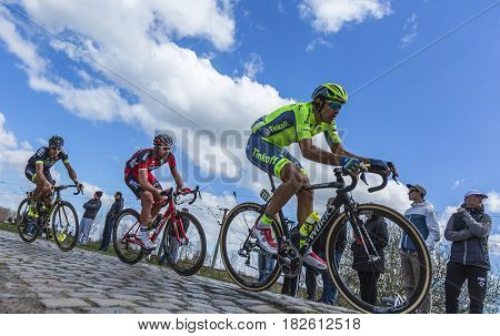 Hornaing France - April 102016: Two cyclists Nikolay Trusov of Tinkoff Rick Zabel of BMC Team and Benoit Jarrier of Fortuneo-Vital Concept Team riding in the peloton on a paved road in Hornaing France during Paris Roubaix on 10 April 2016.