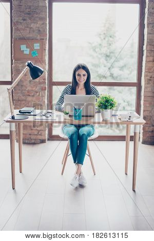 Vertical Photo Of Beautiful Young Woman Sitting At The Table In Modern Workspace And Using Computer