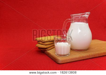 Milk in a ewer and a glass on a red background