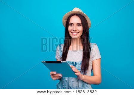 Pretty Smiling Woman In Jeans Overalls And Summer Hat Holding Digital Tablet And Trying To Find Good