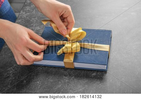 Woman decorating book with ribbon as gift on gray table