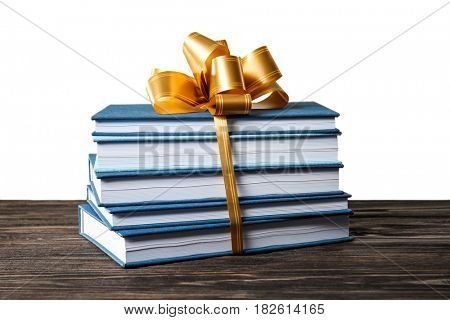 Stack of books with ribbon as gift on wooden table