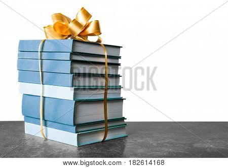 Stack of books with ribbon as gift on gray table