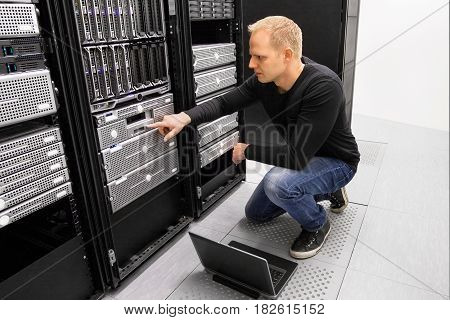 It engineer or consultant working with laptop and maintaining servers in data center.