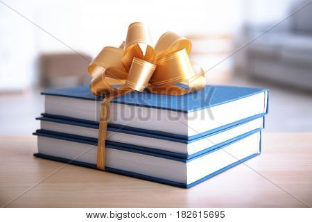 Stack of book with ribbon as gift on wooden table