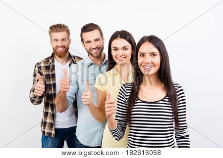 Four Happy Successful  Young Prople Are Showing Thumbs Up On White Background In Casual Clothes And