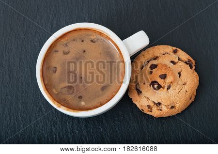 A cup of hot coffee and chocolate pastries, breakfast.
