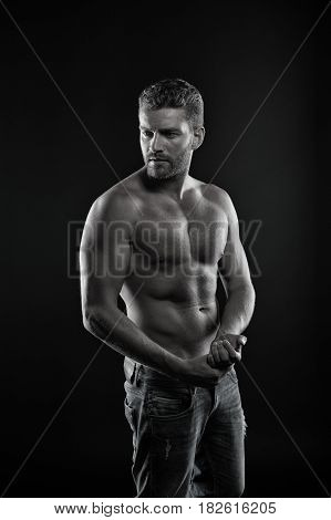 handsome unshaven macho man or sexy muscular guy with athlete body and torso has beard on serious face in jeans black and white
